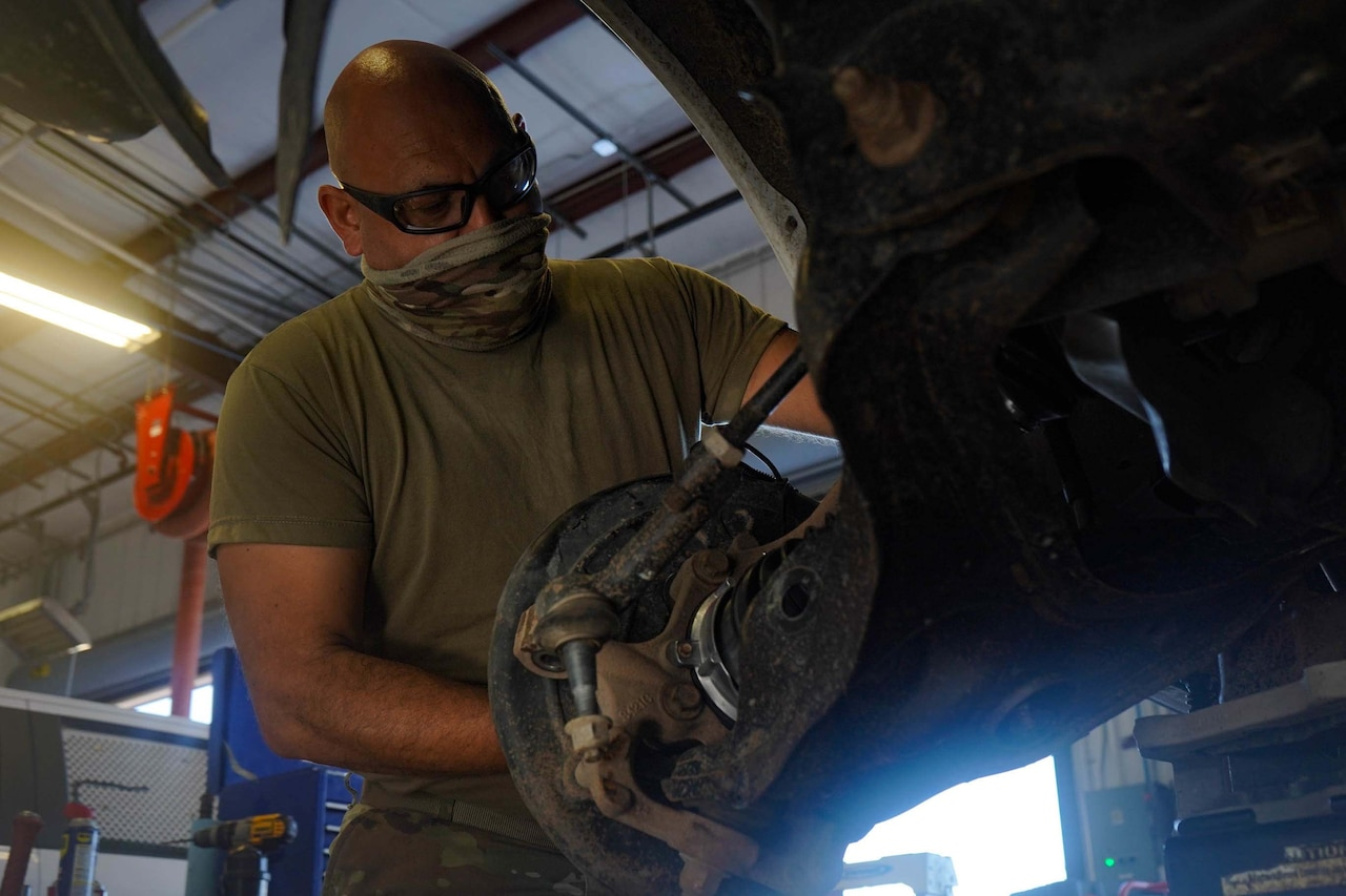 A soldier works on a vehicle.