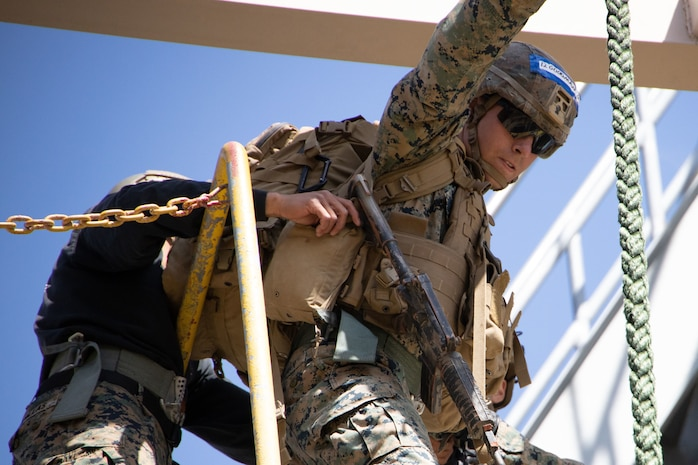 a rifleman with 1st Battalion, 5th Marines, 1st Marine Division, prepares to make a fast rope descent during a Fast Rope Masters Course at Camp Pendleton, California, May 11, 2021.