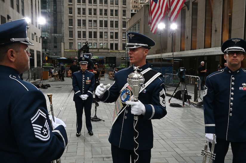 U.S. Air Force Chief Master Sgt. Daniel Valadie, drum major, talks with his fellow members of The United States Air Force Band's Ceremonial Brass before recording for a live TODAY Show broadcast in New York City on July 2, 2021. The official ceremonial ensemble comprises 41 active-duty Airmen who provide musical support for funerals at Arlington National Cemetery, arrivals for foreign heads of state at the White House and Pentagon, patriotic programs, changes of command, retirements, and awards ceremonies. (U.S. Air Force photo by Staff Sgt. Kayla White)
