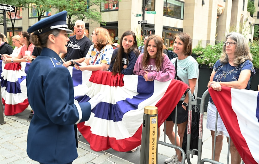 U.S. Air Force Capt. Christina Muncey, premier band flight commander and associate conductor with The United States Air Force Band, engages with audience members before leading the Ceremonial Brass during a live broadcast on the TODAY Show in New York City July 2, 2021. The official ceremonial ensemble comprises 41 active-duty Airmen who provide musical support for funerals at Arlington National Cemetery, arrivals for foreign heads of state at the White House and Pentagon, patriotic programs, changes of command, retirements, and awards ceremonies. (U.S. Air Force photo by Staff Sgt. Kayla White)