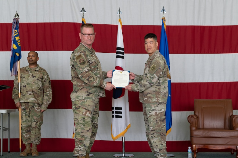 Col. Brian Moore, 51st Maintenance Group commander, left, presents the Meritorious Service Medal to Maj. Hoyoon Chung, 51st Munitions Squadron outgoing commander during the change of command ceremony at Osan Air Base, Republic of Korea, July 6, 2021. Chung earned the Meritorious Service Medal for his conduct as the 51st MUNS commander. (U.S. Air Force photo by Tech. Sgt. Nicholas Alder)
