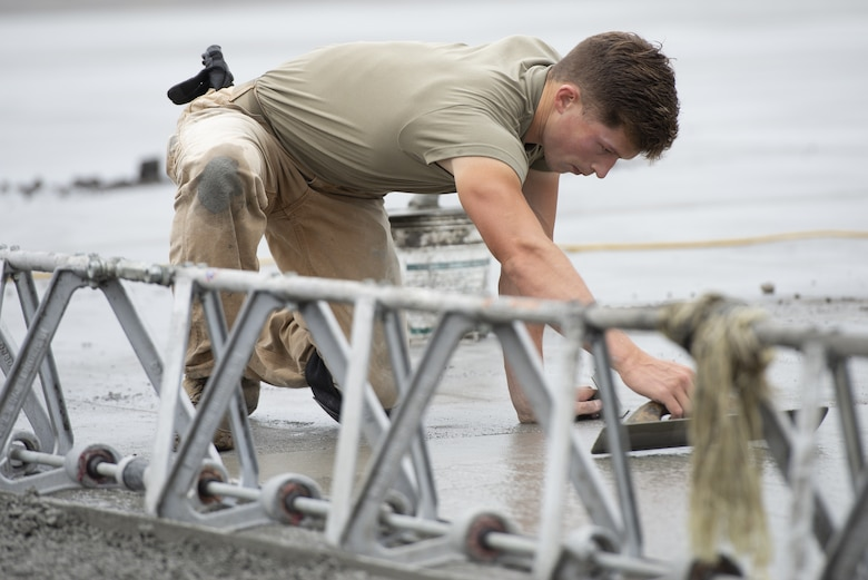 Airman 1st Class Josiah Gomberg, 823d RED HORSE Squadron pavement and equipment construction journeyman, levels wet concrete as part of a construction project to expand a flightline apron June 30, 2021, at Yokota Air Base, Japan. Airmen assigned to the 823rd, 819th and 820th RED HORSE Squadrons, combined efforts to increase aircraft parking capabilities. The apron expansion is the first in an approximately four-year phased construction effort to enhance Yokota Air Base's airlift mission and is the first 800th RED HORSE Group project within the U.S. Indo-Pacific Command. (U.S. Air Force photo by Tech. Sgt. Christopher Hubenthal)