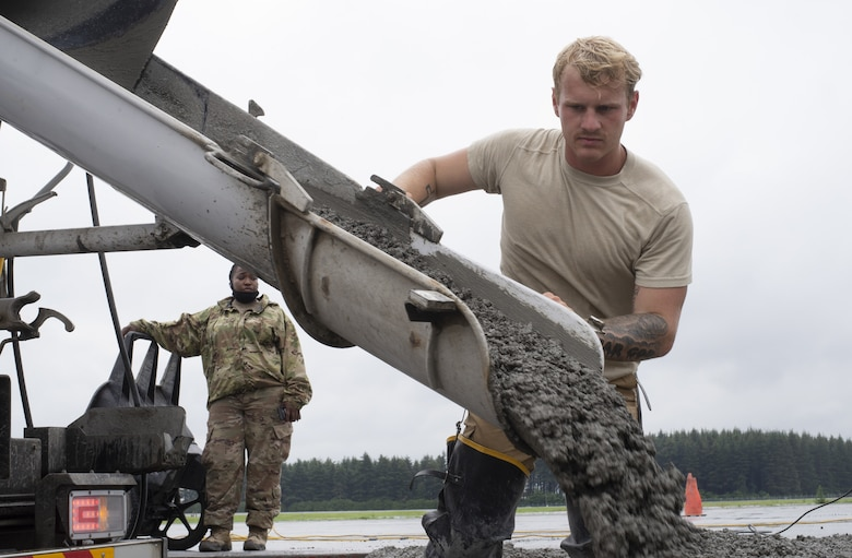 Senior Airman Zeke LaGrou, 823rd RED HORSE Squadron pavement and construction equipment journeyman, distributes wet concrete as part of a construction project to expand a flightline apron June 30, 2021, at Yokota Air Base, Japan. The construction project is the first 800th RED HORSE Group project within the U.S. Indo-Pacific and is led by the 823rd RED HORSE Squadron with support from the 819th and 820th RED HORSE Squadrons. The apron expansion is the first in an approximately four-year phased construction effort to enhance Yokota Air Base's airlift mission capabilities. (U.S. Air Force photo by Tech. Sgt. Christopher Hubenthal)