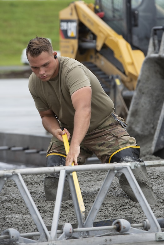 Senior Airman Kendall Allison, 819th RED HORSE Squadron structural journeyman, levels wet concrete as part of a construction project to expand a flightline apron June 30, 2021, at Yokota Air Base, Japan. The construction project requires Airmen assigned to the 823rd, 819th and 820th RED HORSE Squadrons to pour approximately 7,300 cubic meters of concrete and pave 650 tons of asphalt in a construction effort to increase aircraft parking capabilities at Yokota Air Base. The apron expansion is the first in an approximately four-year phased construction effort to enhance Yokota Air Base's airlift mission capabilities. (U.S. Air Force photo by Tech. Sgt. Christopher Hubenthal)