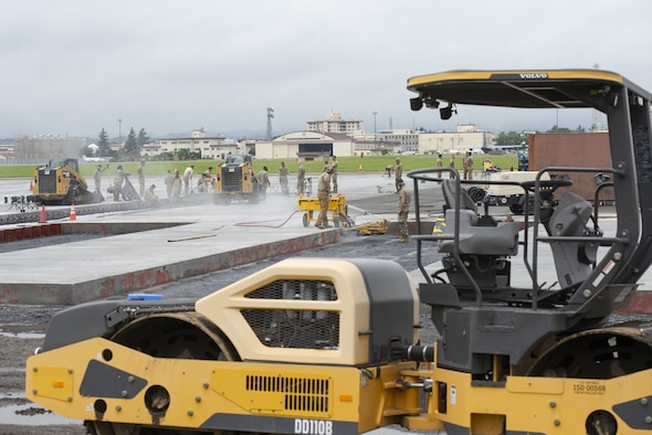 Airmen assigned to the 800th RED HORSE Group, work together in a construction effort to expand a flightline apron June 30, 2021, at Yokota Air Base, Japan. The construction project requires Airmen assigned to the 823rd, 819th and 820th RED HORSE Squadrons to pour approximately 7,300 cubic meters of concrete and pave 650 tons of asphalt in a construction effort to increase aircraft parking capabilities at Yokota Air Base. The apron expansion is the first in an approximately four-year phased construction effort to enhance Yokota Air Base's airlift mission capabilities. (U.S. Air Force photo by Tech. Sgt. Christopher Hubenthal)