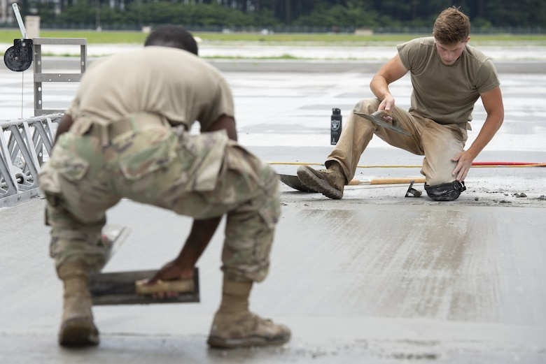 Airman 1st Class Josiah Gomberg, background, 823rd RED HORSE Squadron pavement and construction equipment journeyman, levels wet concrete as part of a construction project to expand a flightline apron June 30, 2021, at Yokota Air Base, Japan. Airmen assigned to the 823rd, 819th and 820th RED HORSE Squadrons, combined efforts to increase aircraft parking capabilities. The apron expansion is the first in an approximately four-year phased construction effort to enhance Yokota Air Base's airlift mission and is the first 800th RED HORSE Group project within the U.S. Indo-Pacific. (U.S. Air Force photo by Tech. Sgt. Christopher Hubenthal)