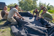 Ukrainian Marines with the 36th Marine Brigade carry a combat rubber reconnaissance craft