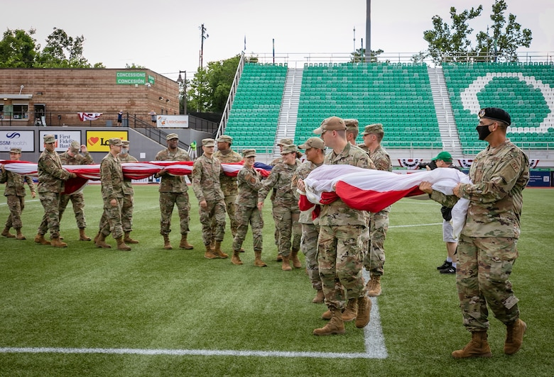 Airmen carry out large U.S. flag on soccer field.