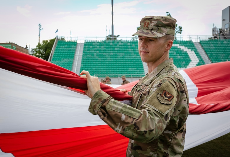 Airman holds section of large U.S. flag at soccer field.