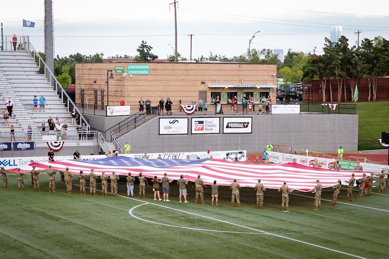 Airman unfurling large U.S. flag on soccer field.