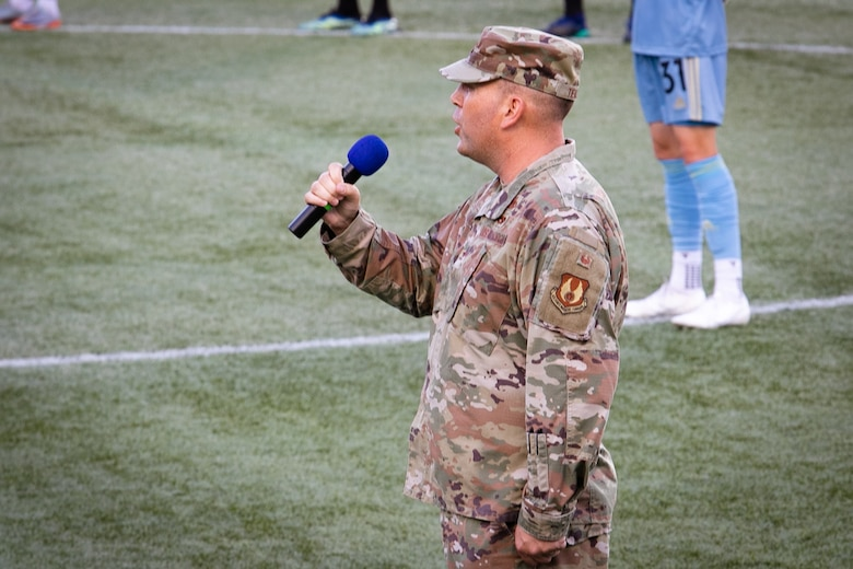 Air Force Colonel singing National Anthem on field.