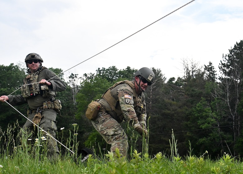 Staff Sgt. Adam Abderrazzaq, 387th explosive ordnance disposal technician, and Michael Rocket, Massachusetts state police department bomb squad trooper, attempt to gain access into a shipping container using remote access techniques during a training scenario at Raven's Challenge Interoperability Exercise June 8, 2021, at Fort Devens Army Base, Devens, Massachusetts. The Soldiers spent a week at the exercise working with civilian public safety bomb squads training in various scenarios, focusing on interoperability between the agencies in operational environments while promoting teamwork and innovation.  (U.S. Air National Guard photo by Senior Airman Sara Kolinski)