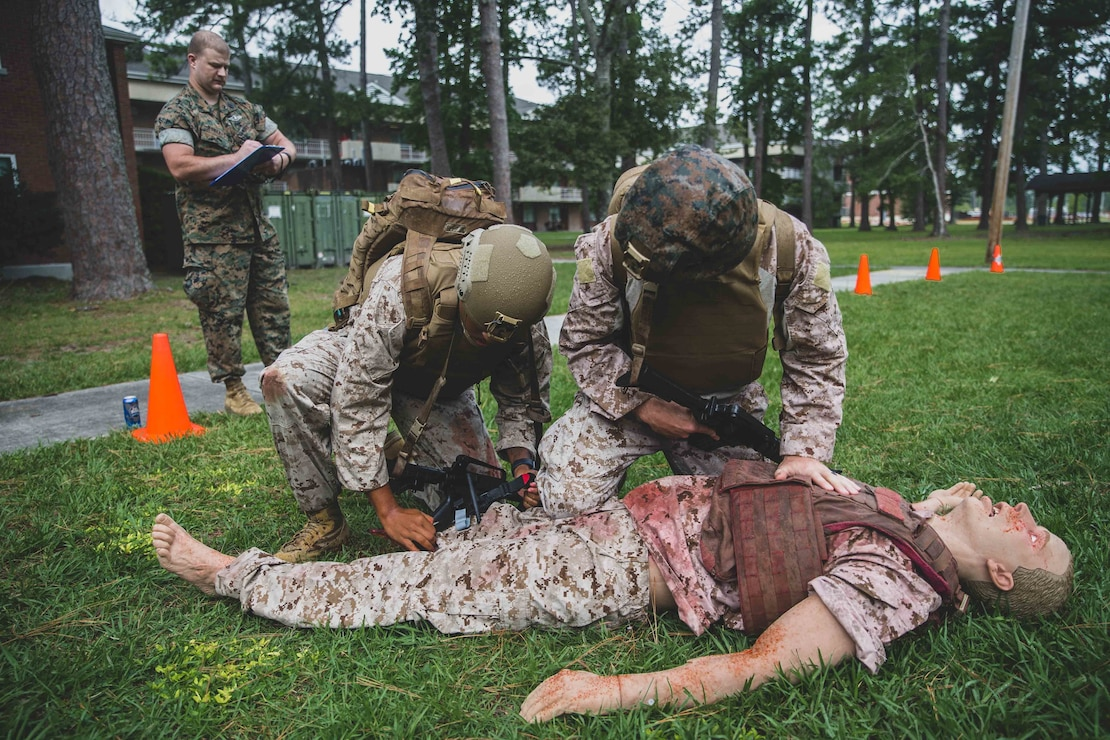 U.S. Navy hospital corpsmen with 1st Battalion, 2d Marine Regiment (1/2), 2d Marine Division (MARDIV), apply a tourniquet to a simulated casualty as part of 2d MARDIV's prolonged casualty care course on Camp Lejeune, N.C., July 2, 2021.The course prepared the sailors to provide efficient care over an extended period of time while under adverse conditions. (U.S. Marine Corps photo by Lance Cpl. Emma L. Gray)