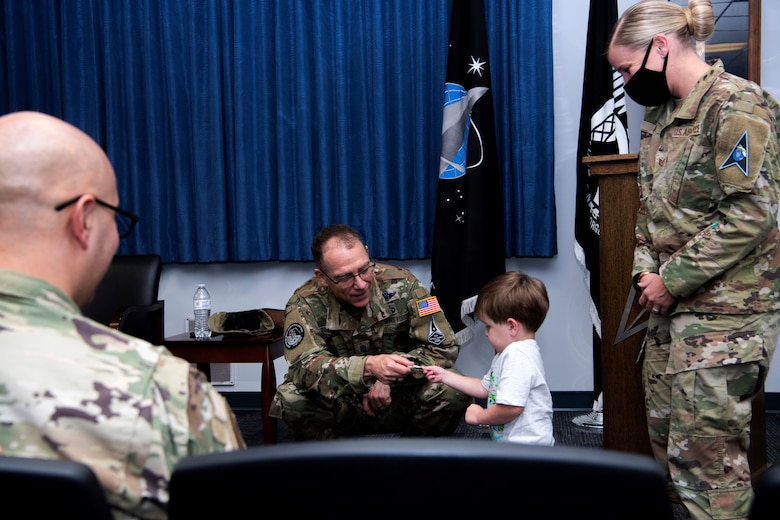 Chief Master Sgt. of the Space Force Roger A. Towberman awards his personal coin to Apollo Meza, 3, son of U.S. Air Force Tech. Sgt. Victoria Meza, Vosler Non-Commissioned Officer Academy Professional Military Education instructor at Peterson Air Force Base, Colorado, July 1, 2021. Towberman presented the VNCOA the Department of the Air Force NCOA of the Year award which recognizes outstanding performance and exceptional contributions that support professional military education across the Air Force. (U.S. Space Force photo by Airman 1st Class Joshua Fontenot)