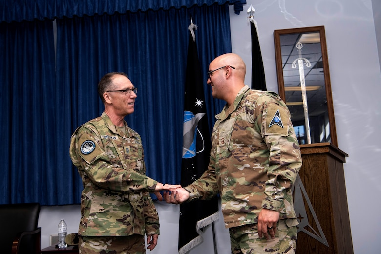 Chief Master Sgt. of the Space Force Roger A. Towberman awards his personal coin to U.S. Space Force Senior Master Sgt. Adrian Gaxiola, Vosler Non-Commissioned Officer Academy director of education, Peterson Air Force Base, Colorado, July 1, 2021. The VNCOA launched the first-ever NCOA virtual in-residence remote course allowing the continuation of professional military education during the COVID-19. The VNCOA coordinated with the Barnes Center for Enlisted Education to validate Community College of the Air Force requirements and develop a virtual education plan which saved the Air Force $1.8 million in temporary duty costs. (U.S. Space Force photo by Airman 1st Class Joshua Fontenot)