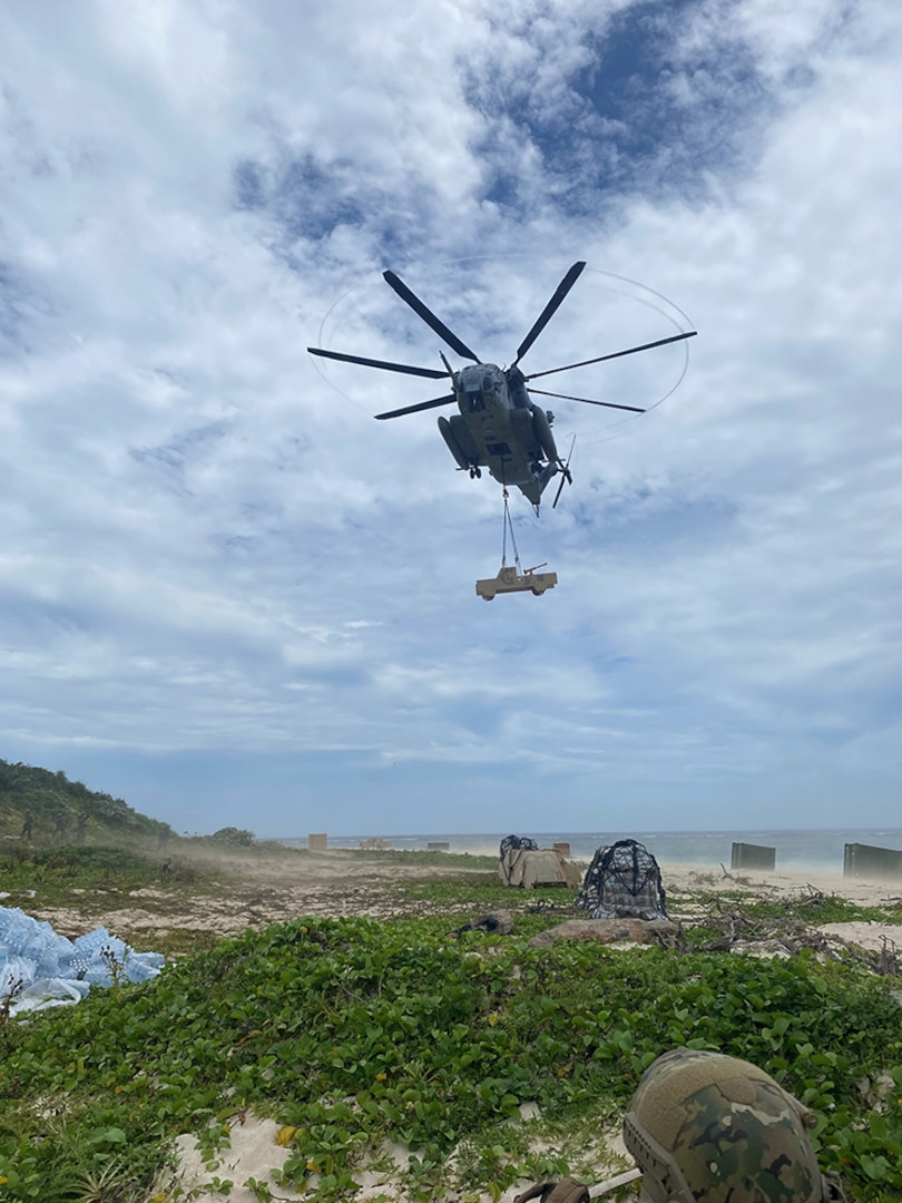 A helicopter drops a fake vehicle on the beach of a tiny island near Okinawa.