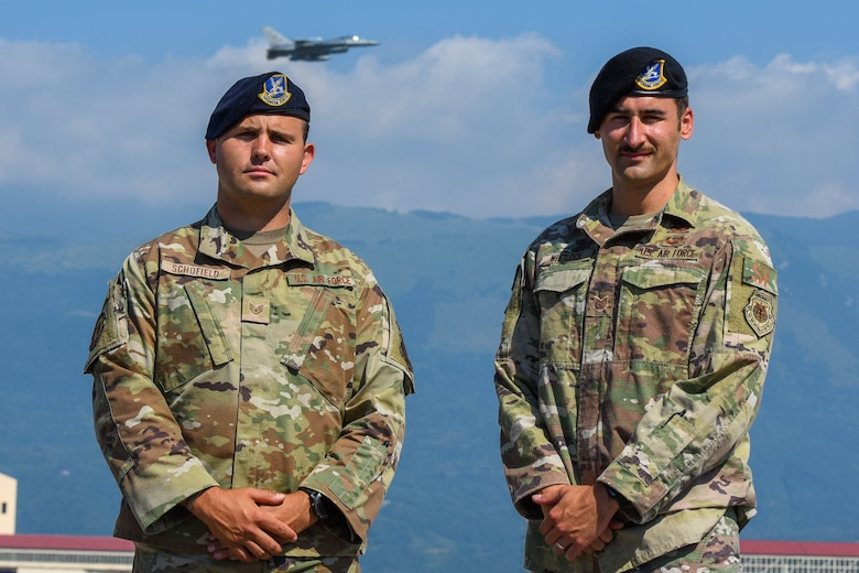 U.S. Air Force Staff Sgt. Levi Schofield, 31st Security Forces Squadron fire team leader, left, and Tech. Sgt.. Jordan Whitlock, 31st SFS squad leader, pose for a photo on the flight line at Aviano Air Base, Italy, July 7, 2021. Whitlock, Schofield and U.S. Air Force Master Sgt. Mario Vaiese, 31st SFS team leader, responded to a head-on collision involving a van and four Moroccan nationals on two mopeds during a temporary duty travel (TDY) in Ben Guerir, Morocco, for exercise AFRICAN LION, June 11, 2021. (U.S. Air Force photo by Airman 1st Class Brooke Moeder)