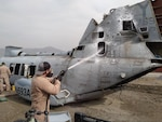 medic sprays helicopter hull with fire suppressing material