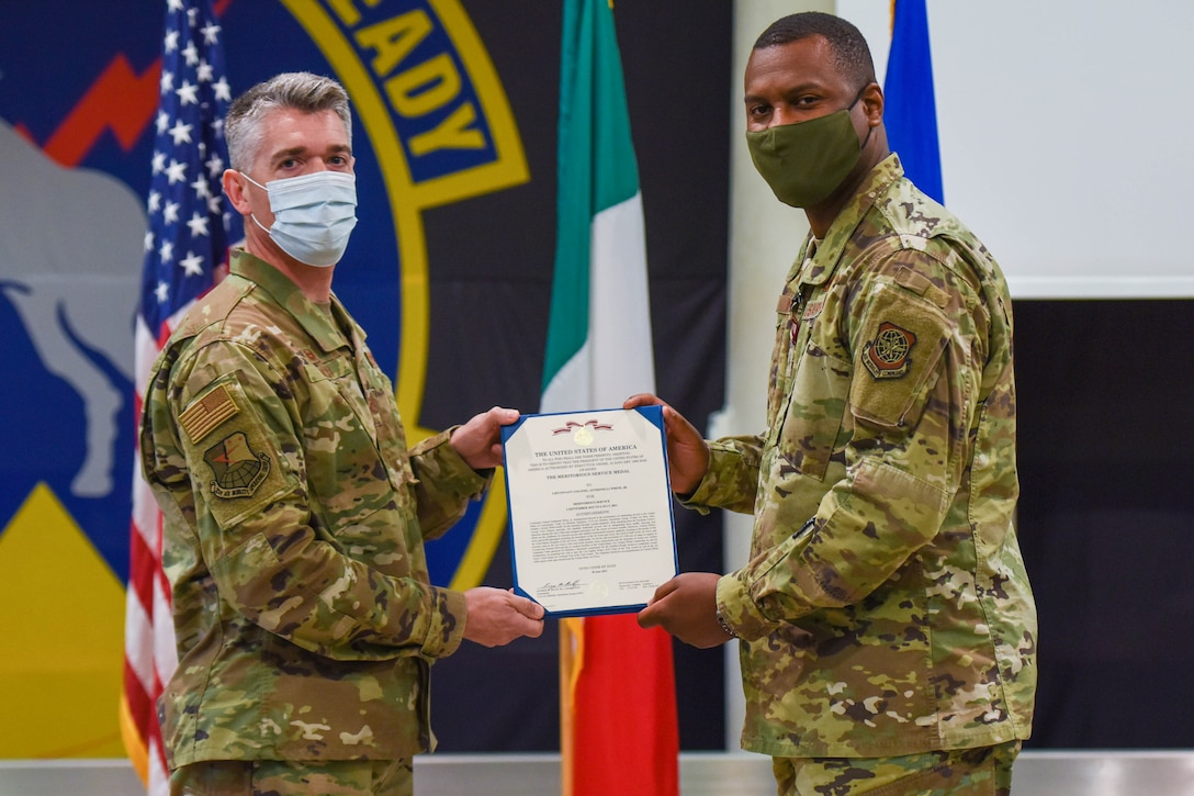 U.S. Air Force Col. Christopher Busque, 31st Mission Support Group commander, left, and U.S. Air Force Lt. Col. Anthonelli White, 724th Air Mobility Squadron outgoing commander, pose for a photo during a change of command ceremony at Aviano Air Base, Italy, July 6, 2021. The 724th AMS is an Air Mobility Command tenant and supports the 31st Fighter Wing through deployments by completing airworthiness inspections, which measures an aircraft's suitability for a safe flight prior to takeoff. (U.S. Air Force photo by Airman 1st Class Brooke Moeder)