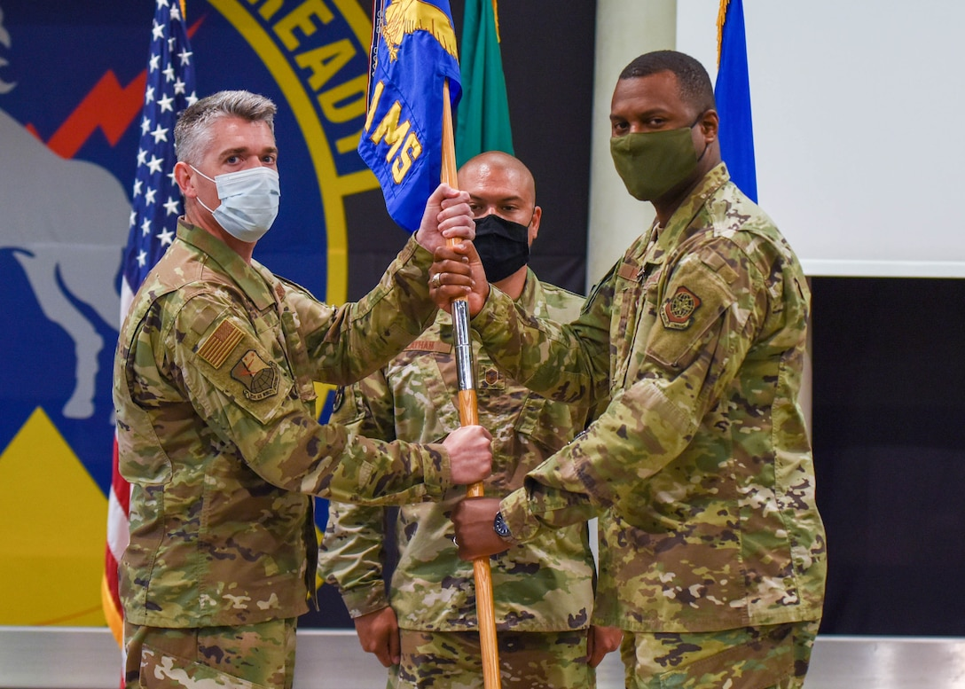 U.S. Air Force Col. Christopher Busque, 31st Mission Support Group commander, left, passes the guidon to U.S. Air Force Lt. Col. Anthonelli White, 724th Air Mobility Squadron outgoing commander, during a change of command ceremony at Aviano Air Base, Italy, July 6, 2021. The 724th AMS has 44 military and civilian employees is the smallest squadron out of 11 air mobility squadrons in the U.S. European Command. (U.S. Air Force photo by Airman 1st Class Brooke Moeder)