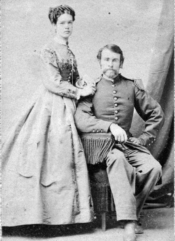 A man in dress uniform sits in a chair. A woman stands beside him, her hand on his shoulder.