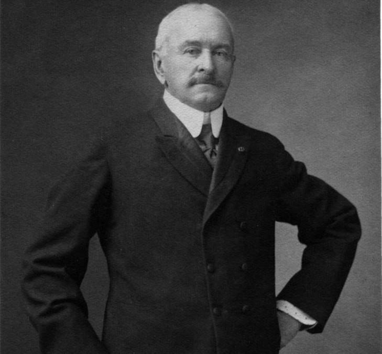 A man standing in a suit jacket rests his hand on his hip.