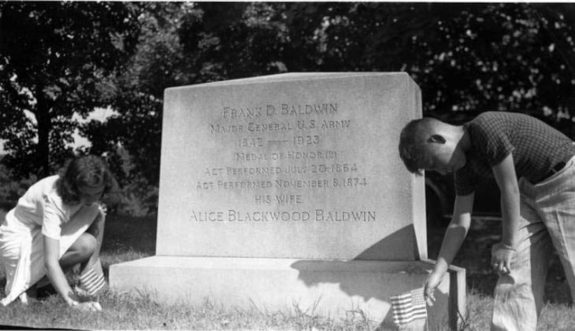 A boy and a woman place small American flags at a grave marker.