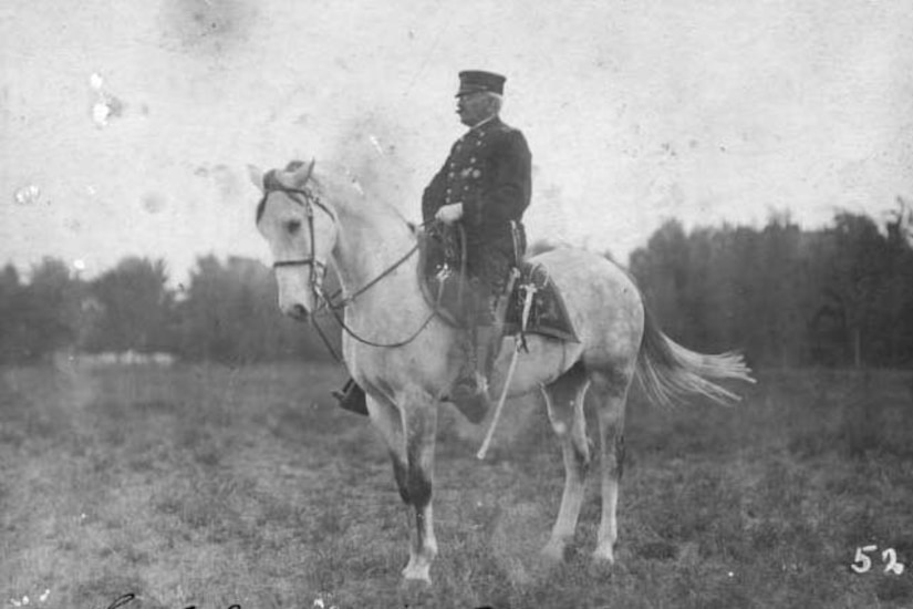 A soldier sits on a horse in a field.