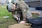 u.s. army soldier uses a knife to lift a piece of cloth.