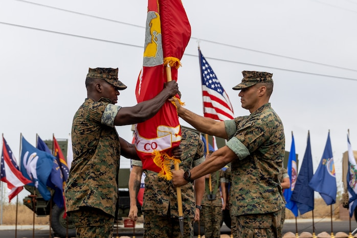 U.S. Marine Corps Lt. Col. Anthony Mercado, right, the outgoing commanding officer of 1st Air Naval Gunfire Liaison Company (1st ANGLICO), I Marine Expeditionary Force Information Group, passes the organizational colors to the oncoming commanding officer of 1st ANGLICO, Lt. Col. McDaniel Sharber during the battalion's change of command ceremony at Marine Corps Base Camp Pendleton, California, June 30, 2021. The ceremony was held to commemorate the passing of command from Lt. Col. Anthony Mercado to Lt. Col. McDaniel Sharber. (U.S. Marine Corps photo by Lance Cpl. Isaac Velasco)
