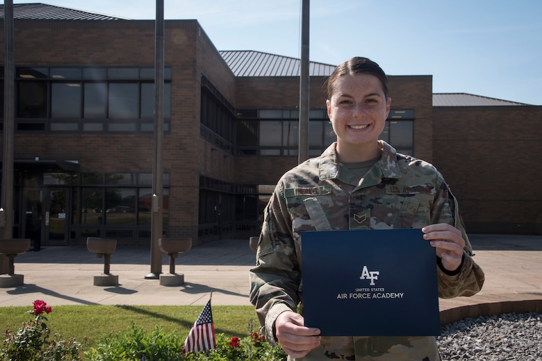Senior Airman Alivia Merkel, a dental technician at the 179th Airlift Wing, stands outside wing headquarters holding her letter of acceptance to the Air Force Academy at the 179th Airlft Wing in Mansfield, Ohio, June 23, 2021