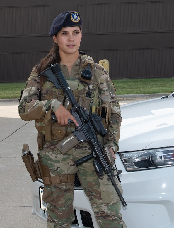 Close up of female Airman in uniform standing guard in front of Security Forces vehicle as she holds her weapon. Female is wearing new body armor for women