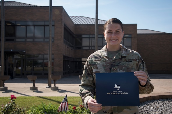 Senior Airman Alivia Merkel, a dental technician at the 179th Airlift Wing, stands outside wing headquarters holding her letter of acceptance to the Air Force Academy at the 179th Airlft Wing in Mansfield, Ohio, June 23, 2021. After three years of service at the 179th Airlift Wing, Merkel has been offered an opportunity to further her education while commissioning in the World's Greatest Air Force. (U.S. Air National Guard photo by Airman First Class Grace Riegel)