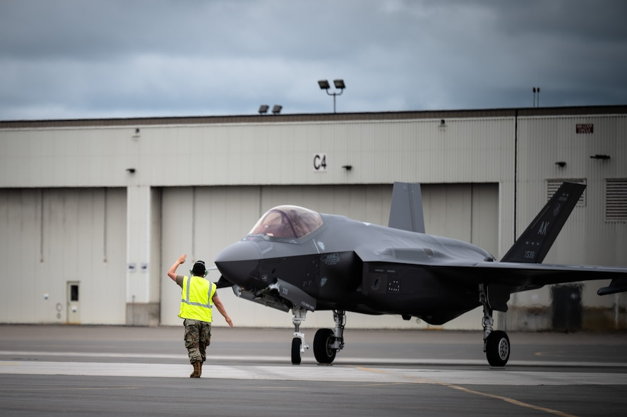 U.S. Air Force Staff Sgt. Michael King, a 356th Aircraft Maintenance Unit crew chief, marshals an F-35A Lightning II assigned to the 355th Fighter Squadron during a hot pit refuelling on Eielson Air Force Base, Alaska, July 7, 2021.