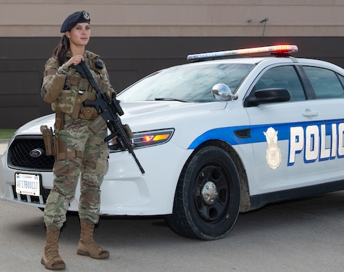 Female Airman in uniform standing guard while holding her weapon, in front of a security forces police car with it's lights flashing. Airman wearing new body armor specifically designed for women
