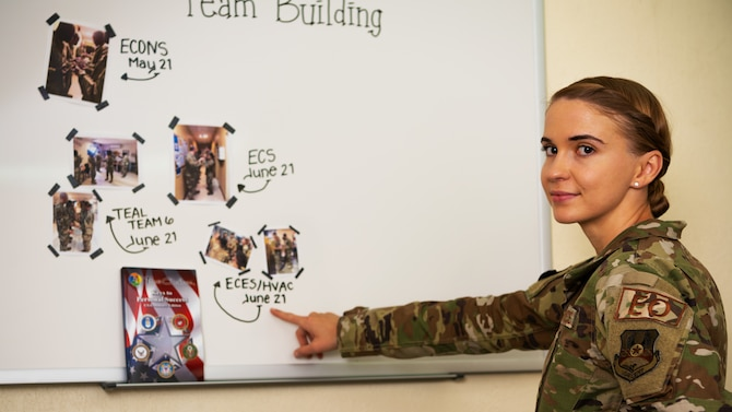 Tech. Sgt. Flavia Carver, 380th Air Expeditionary Wing Equal Opportunity director, points out photos of team building activities conducted by trained diversity and inclusion facilitators at Al Dhafra Air Base, United Arab Emirates, July 7, 2021. The Office of Diversity and Inclusion was established based on the recommendations of both the Office of Secretary of Defense and Air Force Inspector General independent review of racial disparity.