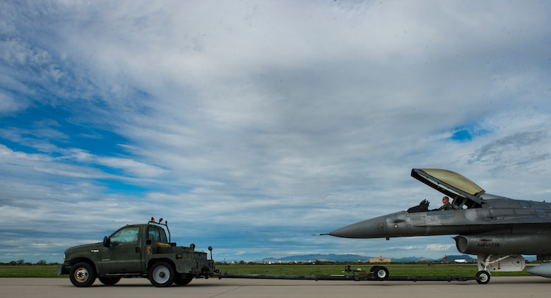 An F-16 Fighting Falcon is towed to the runway before takeoff, Aug 1, 2017 at Davis-Monthan Air Force Base, Ariz. The F-16 was pulled out of storage at the 309th Aerospace Maintenance and Regeneration Group and refurbished to fight status before being transported to Cecil Field, Jacksonville, Fl. where it will be converted into a QF-16 unmanned aerial target. (U.S. Air Force photo by Tech. Sgt. Perry Aston)