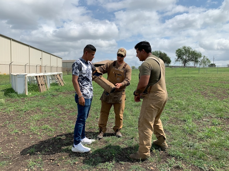 Airmen help student put on arm sleeve for an MWD demonstration.