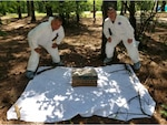 Kentucky Army National Guard Col. Jesse Huff, the outgoing preventive medicine officer for the Kentucky Medical Detachment, and Capt. Bryan Parker, the incoming preventive medicine officer, use a cardboard box with dry ice to bait ticks for collection at Wendell H. Ford Regional Training Center, Greenville, Kentucky, June 1, 2021. Huff has been collecting ticks to aid in prevention of tick-borne illnesses for more than 20 years. (photo by U.S. Army National Guard Sgt. Lance Mudd)