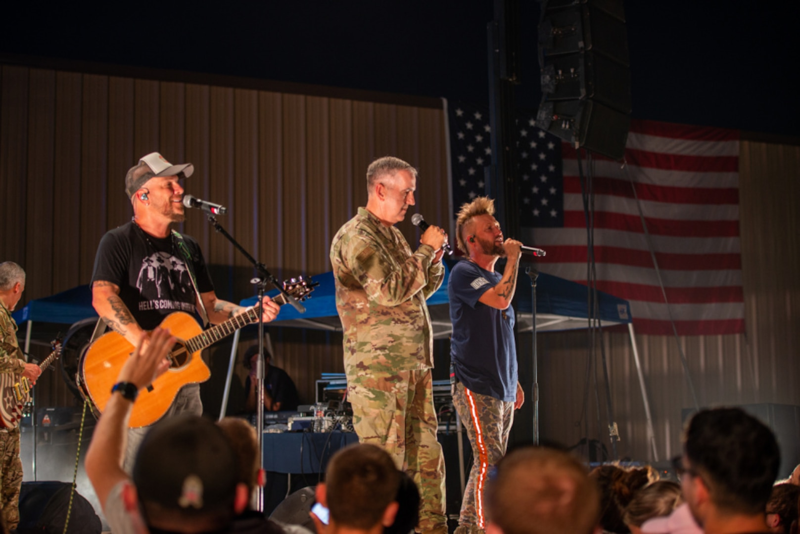 U.S. Air Force Gen. John E. Hyten performs on stage with the band LOCASH during the USO Summer Tour at Joint Base San Antonio-Lackland.
