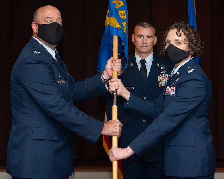 Col. Patrick Miller, 88th Air Base Wing and installation commander, presents the 88th Mission Support Group guidon to Col. Sirena Morris as she assumes command during a ceremony July 1 in the Wright-Patterson Club. (U.S. Air Force photo by R.J. Oriez)