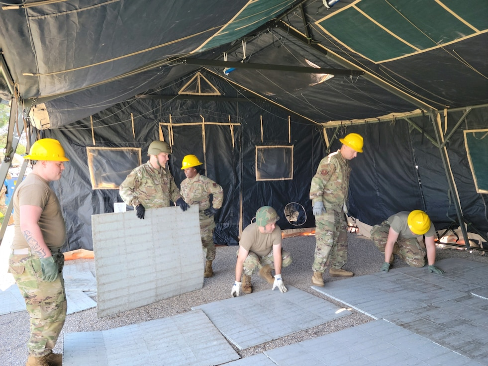 Members from the 118th Force Support Squadron assemble flooring in a temper tent June 10, 2021 at Gowen Field Air National Guard Base, Boise, Idaho. 118th FSS members trained with 124th Fighter Wing members on setting up expeditionary kitchens, conducting search and recovery, and setting up temper tents. (U.S. Air National Guard courtesy photo by Staff Sgt. Elizabeth Martin)