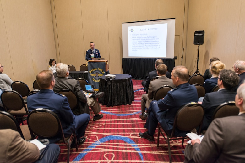 Maj. Chris Backus, a pilot-physician, briefs a group of doctors during an aerospace medicine conference in New Jersey, April 28, 2016. Pilot-Physicians are involved in the research, development, testing, and evaluation of new and current Air Force systems and missions as early as possible to realize the greatest effectiveness and cost savings. Because of unique medical and human factors qualifications pilot-physicians are particularly well-suited to help develop new aircraft, life support equipment, and avionics or software upgrades, and to ensure that changing missions can be accommodated by crews and aircraft. (U.S. Air Force photo/Master Sgt. Brian Ferguson)