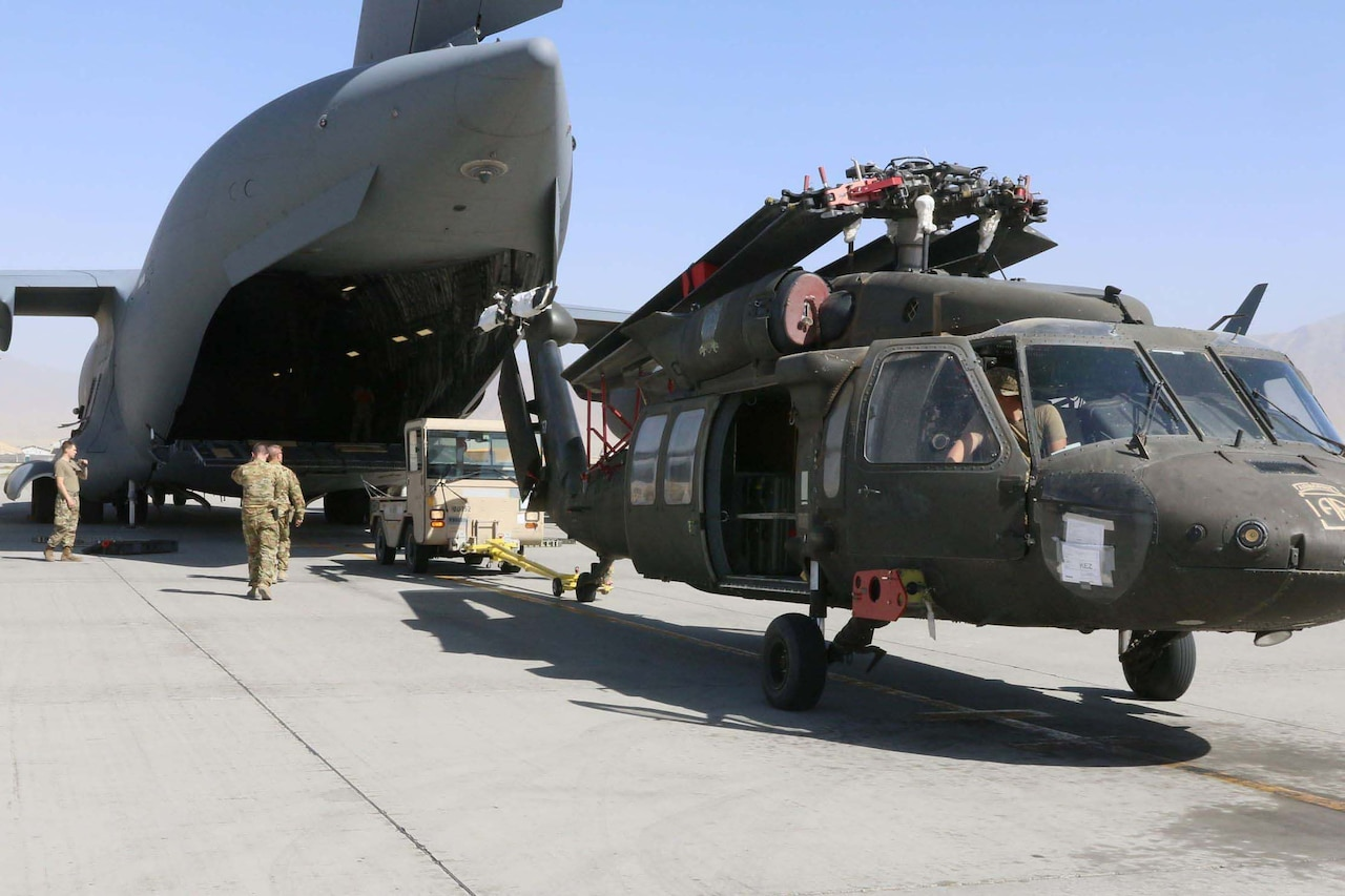 Troops load a helicopter into an airplane.
