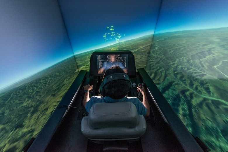 Zach Demers, an aerospace engineer, demonstrates the automatic ground collision avoidance system in an F-16 flight simulator at the Air Force Research Laboratory, Wright-Patterson Air Force Base, Ohio, April 18. Auto GCAS is designed to automatically pull a jet away from the ground if a pilot is disoriented or unable to do so. (U.S. Air Force photo/Master Sgt. Brian Ferguson)