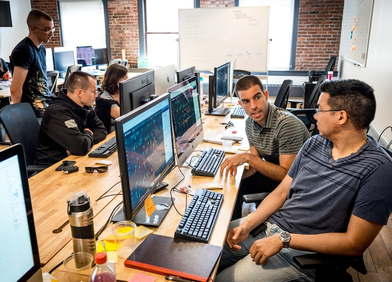 Senior Airman Sean Armstrong, software engineer, and Maj. Drew Armstrong, right, a data scientist, discuss a software development project at the office of Kessel Run, a program within the Defense Innovation Unit Experimental, a United States Department of Defense organization, in Boston May. 30, 2018. Air Force software coders have been learning private sector techniques, such as coding in an open environment to encourage constant collaboration and communication, in order to deliver software solutions to the warfighter in weeks and months instead of years. (U.S. Air Force photo by J.M. Eddins Jr.)