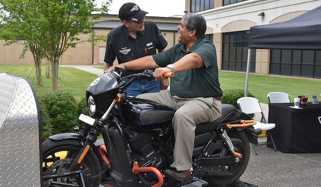 Rafael Santos, chief of the U.S. Army Space and Missile Defense Command's Military Personnel Division, learns about motorcycle safety from Paul Walker, Redstone Harley Davidson, at the USASMDC Safety and SHARP Awareness Day at the command's Redstone Arsenal, Alabama, headquarters June 29, 2021. (U.S. Army photo by Jason Cutshaw)