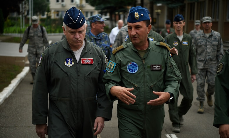 U.S. Air Force Lt. Gen. Scott Rice, left, Air National Guard director, and Romanian Air Force Gen. Viorel Pană, right, chief of staff, discuss mission priorities on their way to a briefing, at 71st Air Base, Câmpia Turzii, Romania, June 22, 2018. Rice and Chief Master Sgt. Ronald Anderson, ANG command chief, visited the base to learn more about the interoperability of the U.S. and Romanian air forces and thank the guardsmen stationed there in support of Operation Dacian Eagle 2018. (U.S. Air Force photo by Staff Sgt. Joshua R. M. Dewberry)