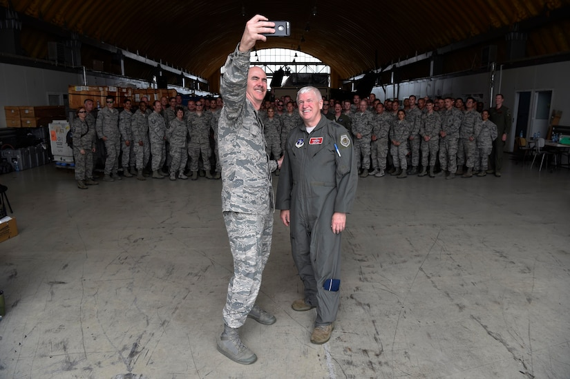 U.S. Air Force Lt. Gen. Scott Rice, right, Air National Guard director, and Chief Master Sgt. Ronald Anderson, ANG command chief, left, take a selfie with guard Airmen from the 131st Expeditionary Fighter Squadron, Massachusetts Air National Guard, deployed to Câmpia Turzii, Romania, as part of a Theater Security Package, June 22, 2018. The guard, flying the F-15C Eagle, and the Romanian Air Force, flying the MiG-21 LanceR, work together during joint training missions. (U.S. Air Force photo by Staff Sgt. Joshua R. M. Dewberry) (This photo has been altered for security purposes.)