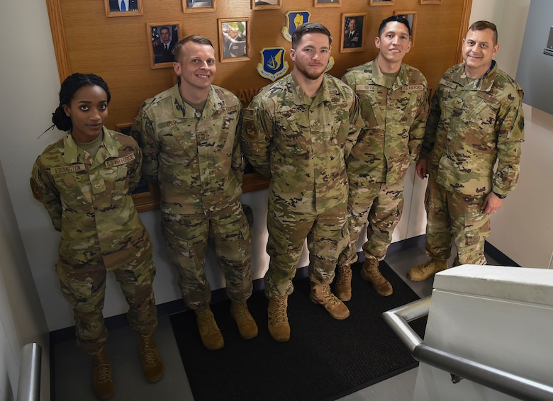 Military members stand side3 by side posing for a picture in front of a leadership photo wall in a stair case.